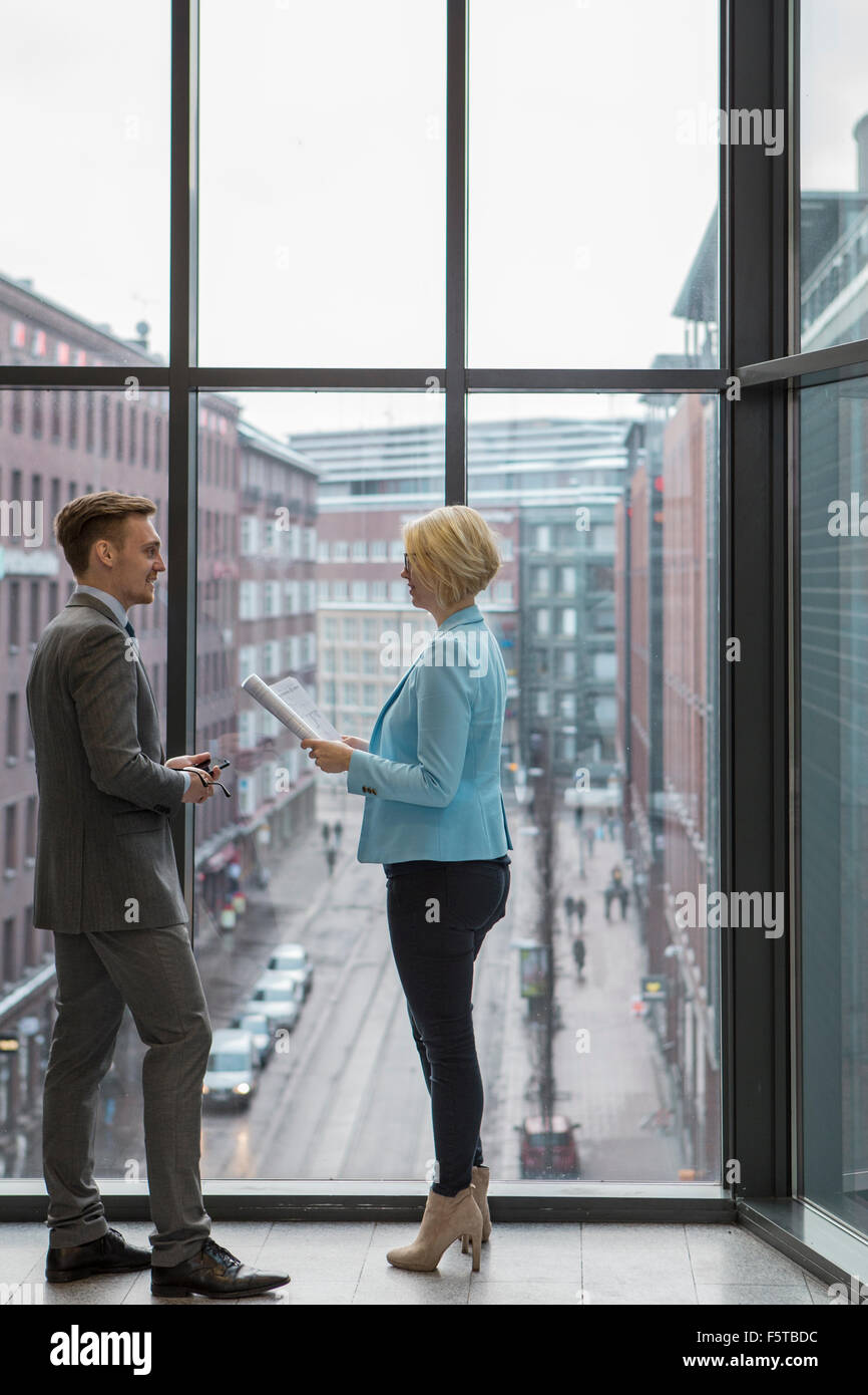 Finland, Helsinki, Business people discussing project by window - Stock Image