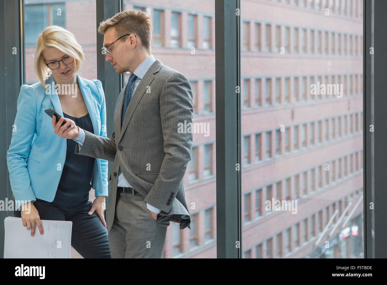 Finland, Helsinki, Business people looking on mobile phone by window - Stock Image