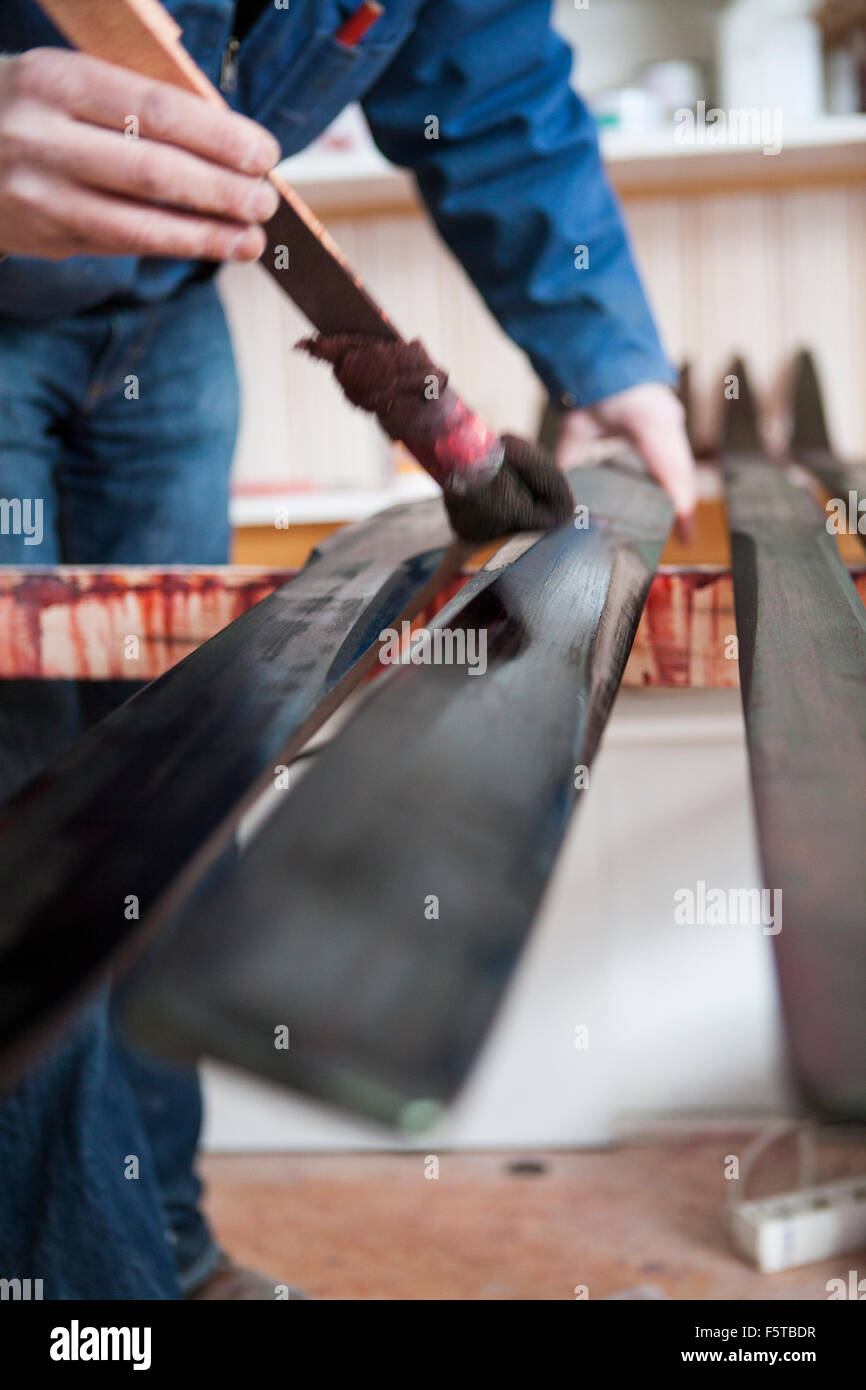 Finland, Close-up of man painting planks with wood stain - Stock Image