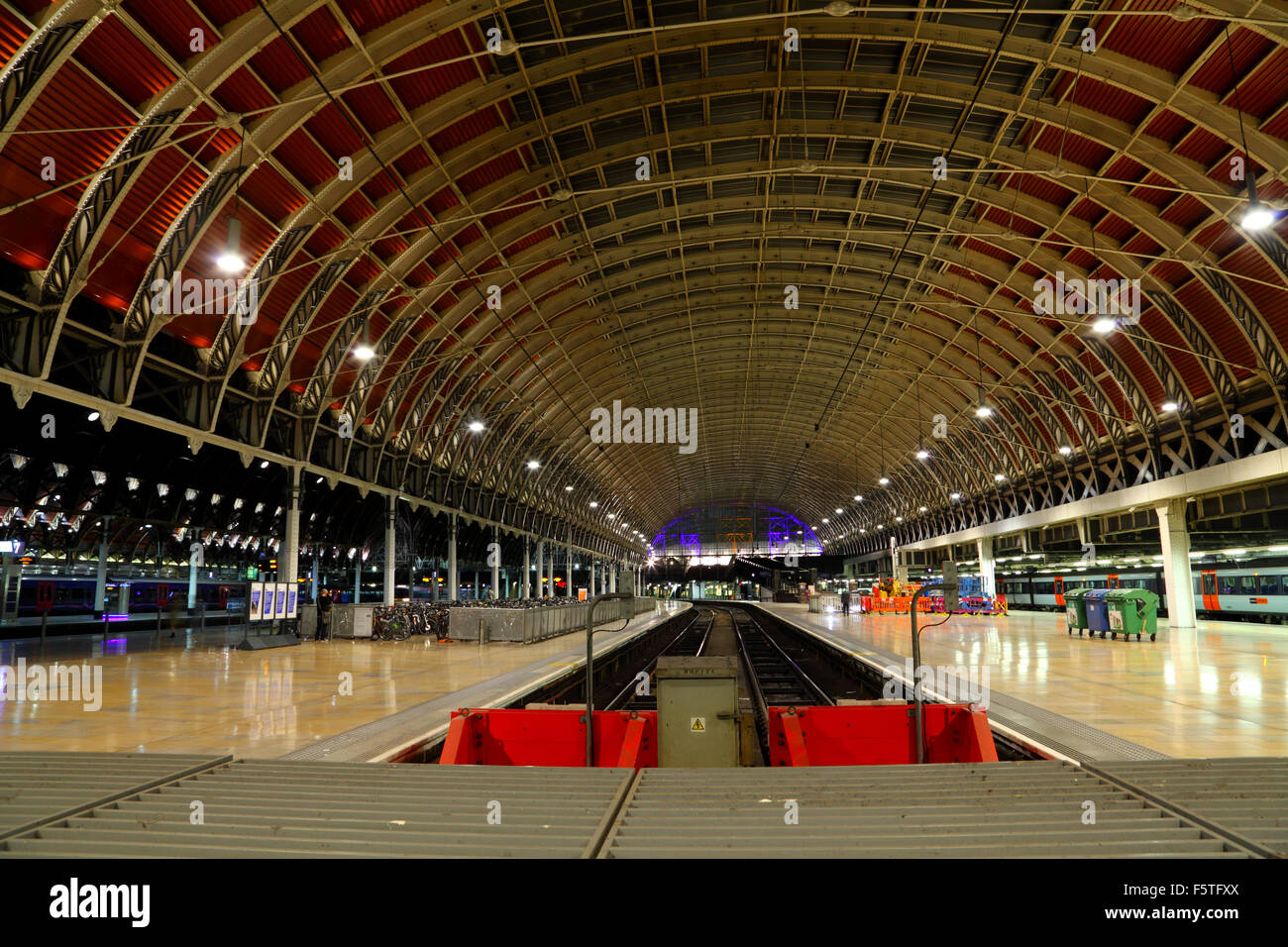 A view looking along platforms 10 and 11 at London Paddington Railway station showing the buffers and lighting at - Stock Image