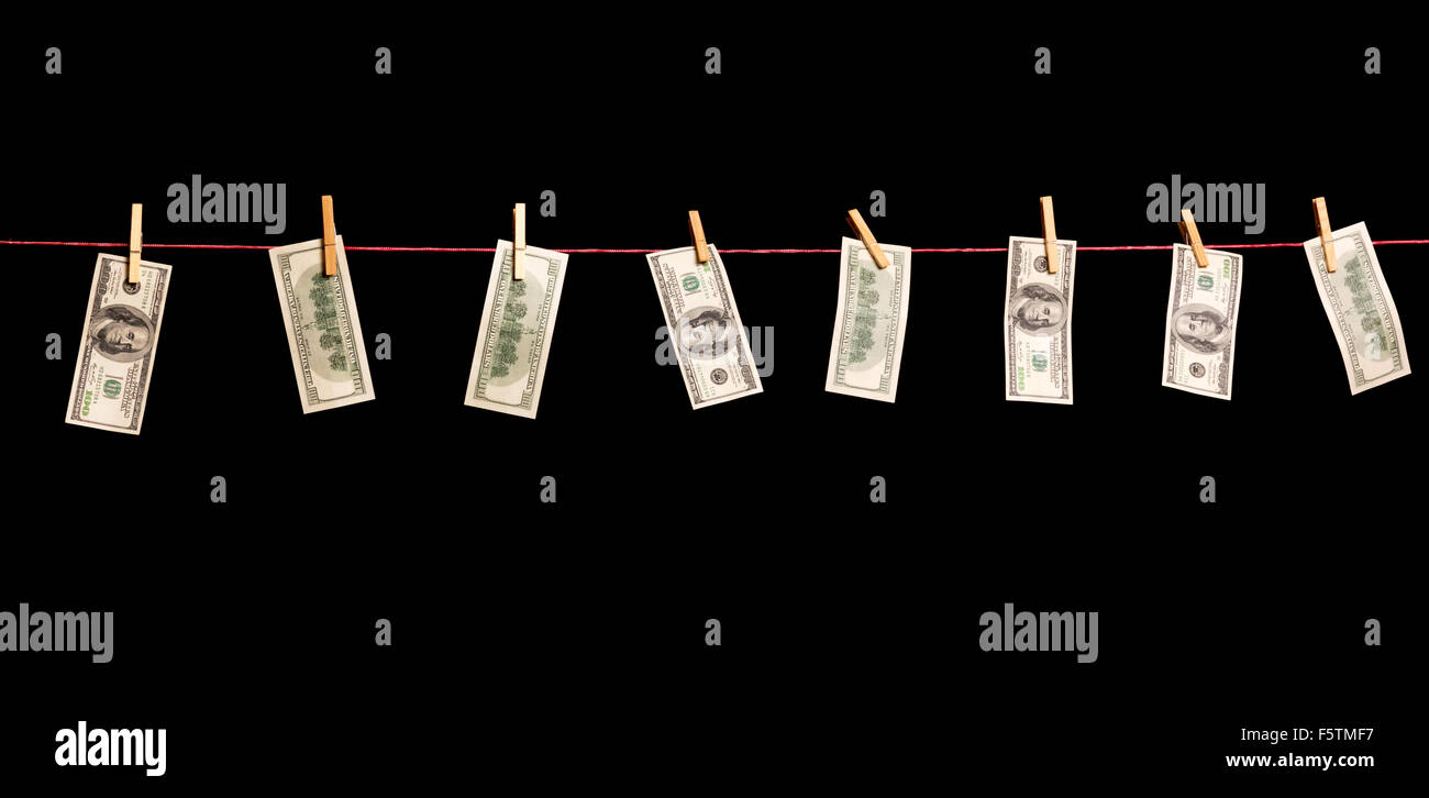 Dollars banknotes are hanging on a rope isolated on black - Stock Image