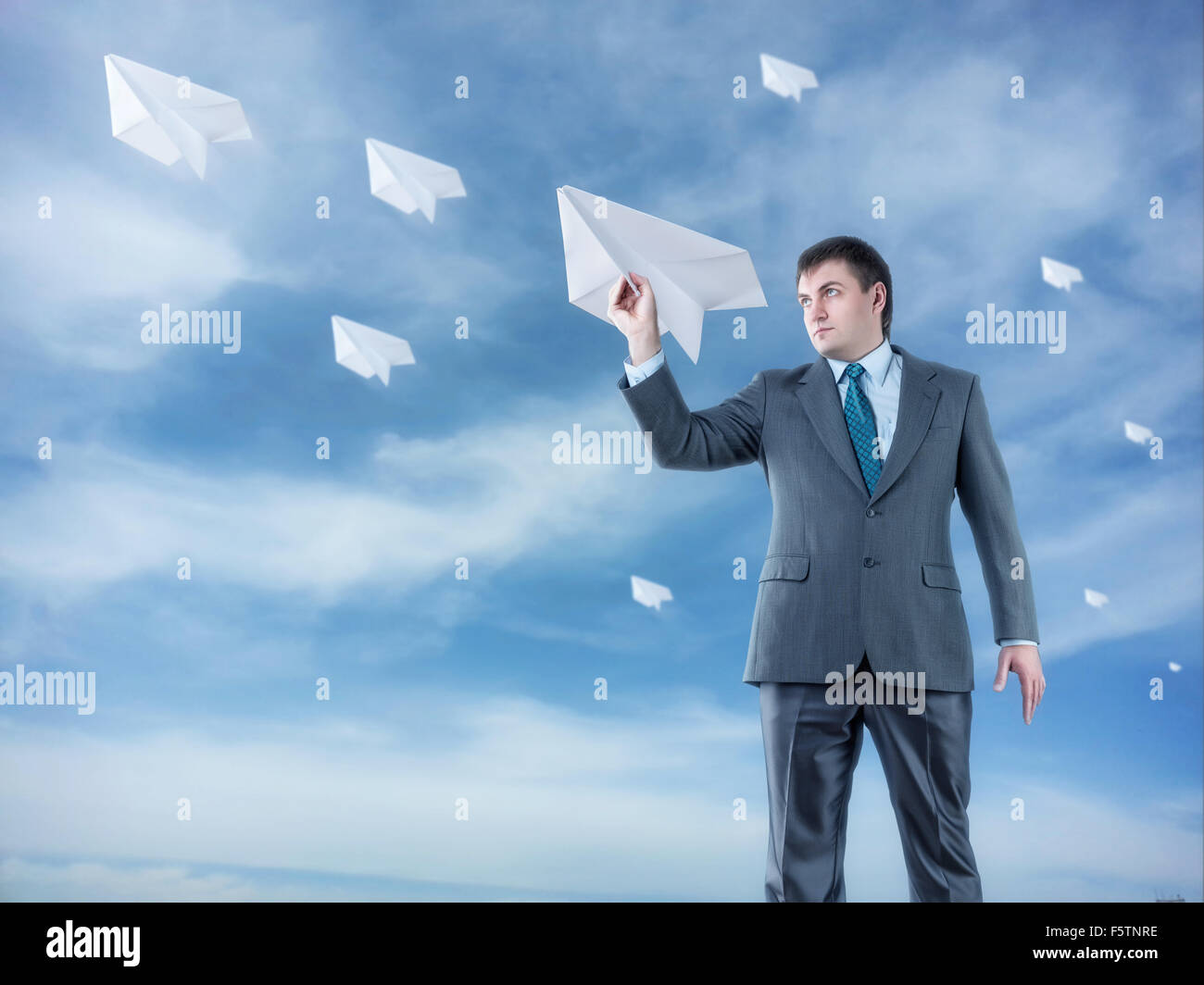 Businessman with big paper plane and isolated on sky background - Stock Image