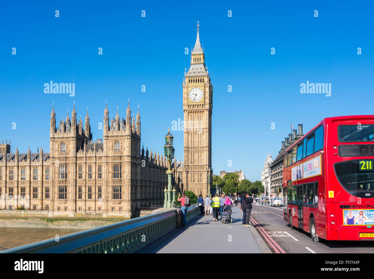 Red bus passing Big Ben Houses of Parliament and Westminster bridge over the River Thames City of London England - Stock Image
