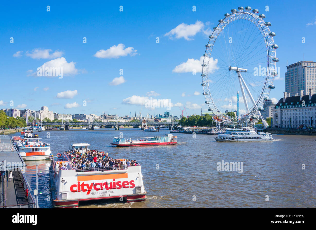 River Thames cruise boats and The London Eye on the South Bank of the River Thames London England GB UK EU Europe - Stock Image