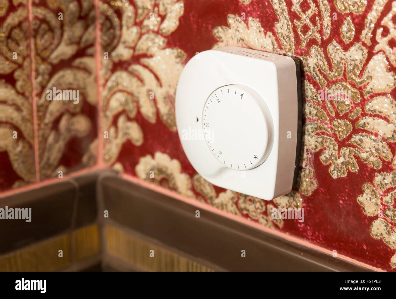 Temperature control on the wall indoors - Stock Image