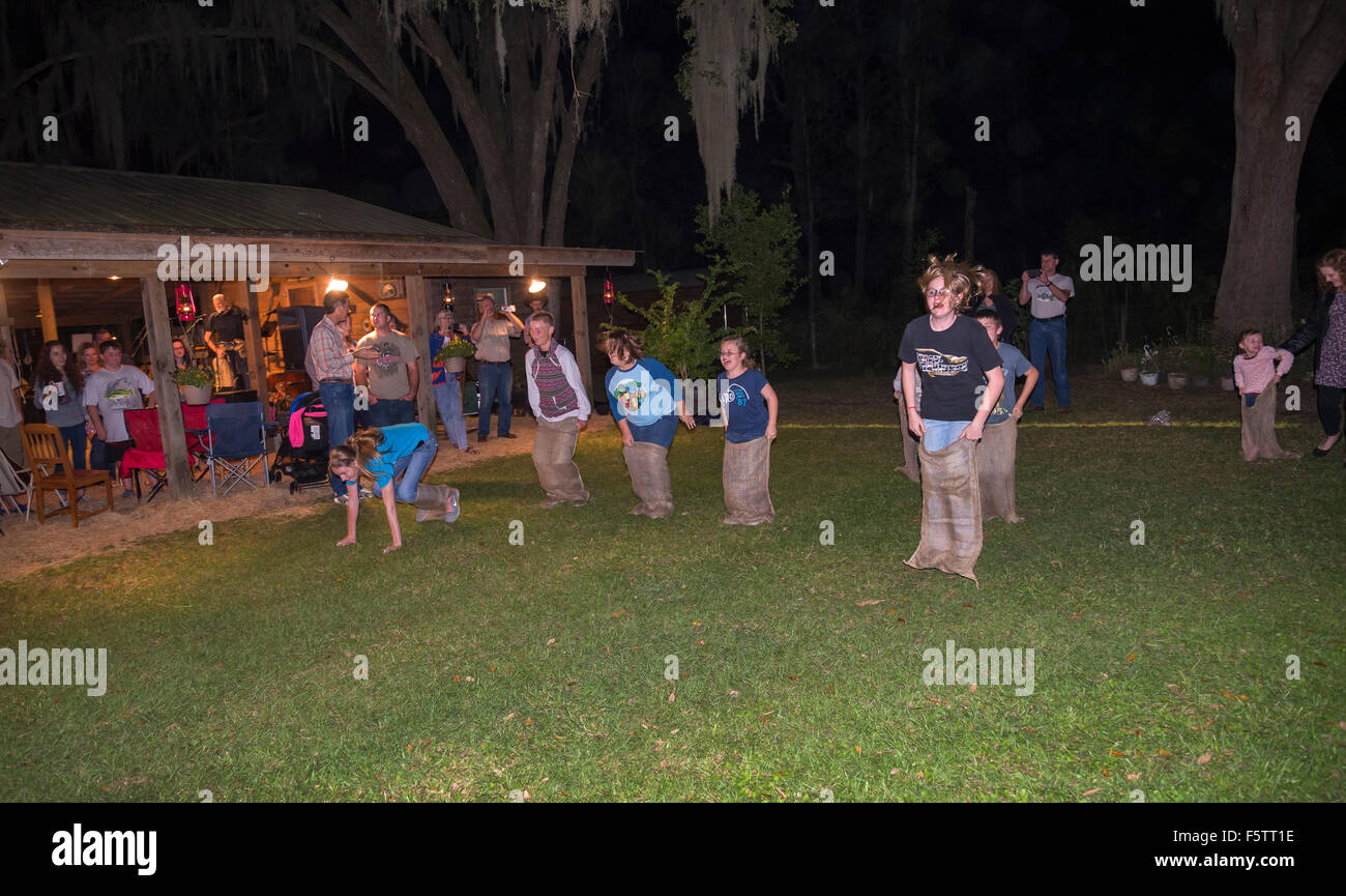 Kids in a sack race during a fall celebration in North Central Florida. - Stock Image