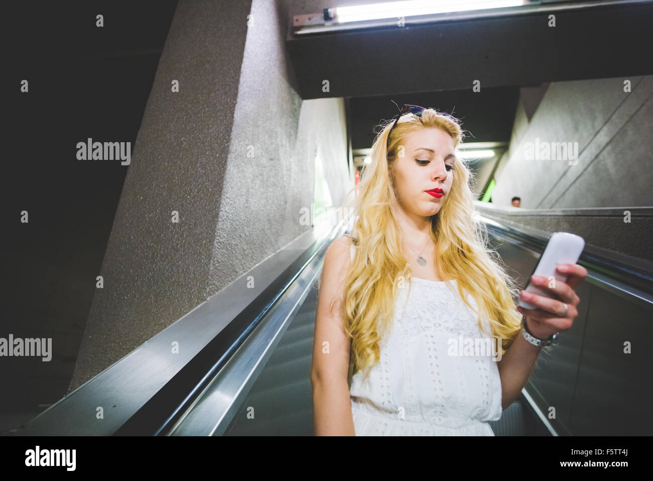 Half length of young handsome caucasian blonde straight hair woman on a escalator in the subway, holding a smartphone, - Stock Image