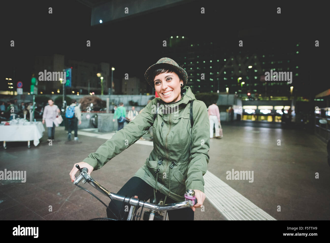 Half length of young handsome caucasian brown straight hair woman riding a bicycle in the night, overlooking right, - Stock Image