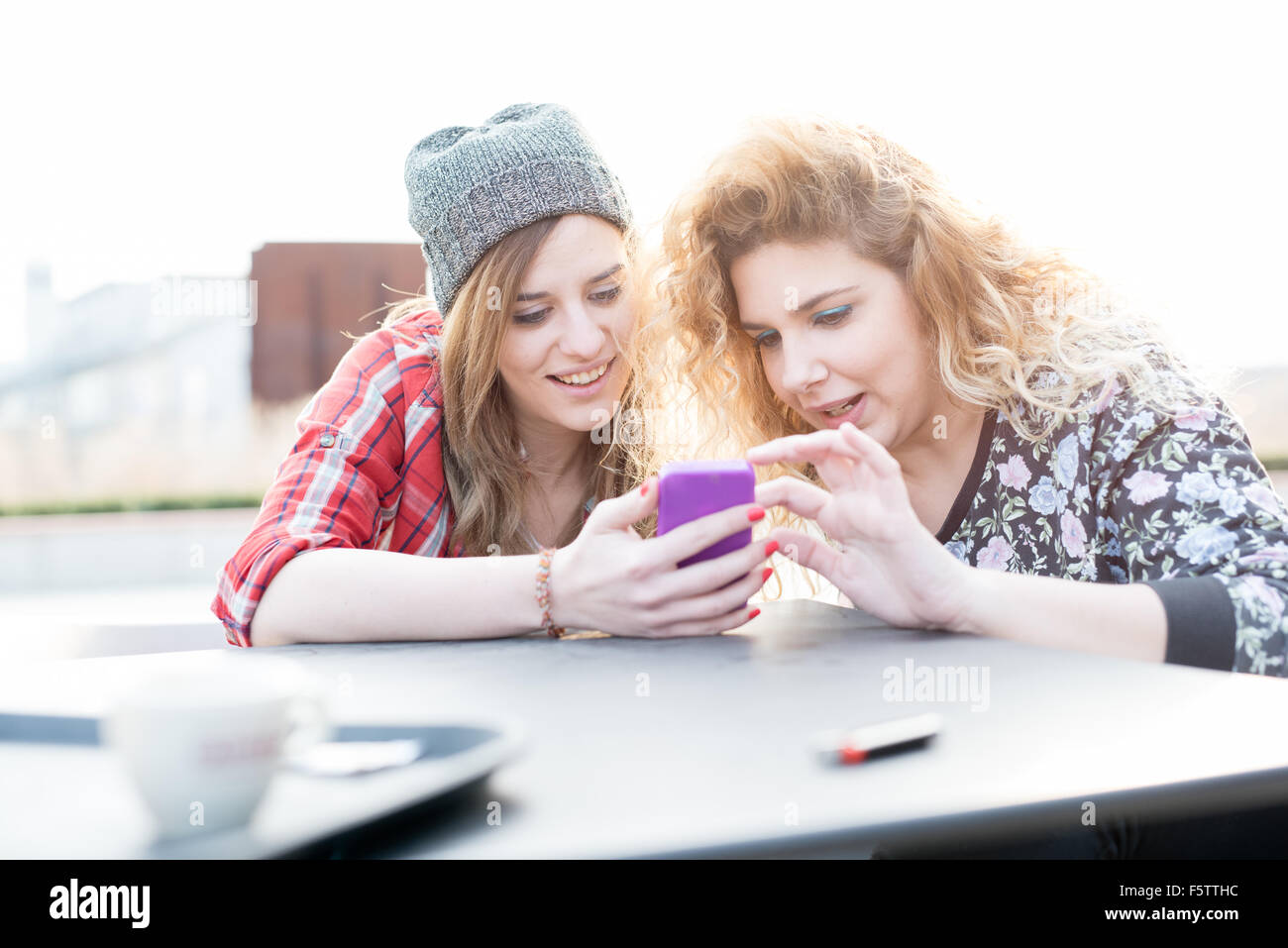 Two young curly and straight blonde hair caucasian woman sitting on a bar, using smartphone, both looking downward - Stock Image