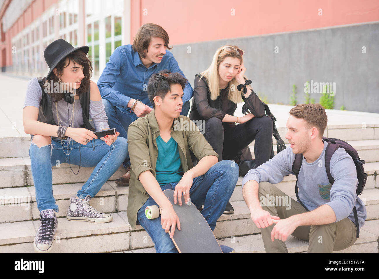 group of young multiethnic friends sitting on a staircase talking to