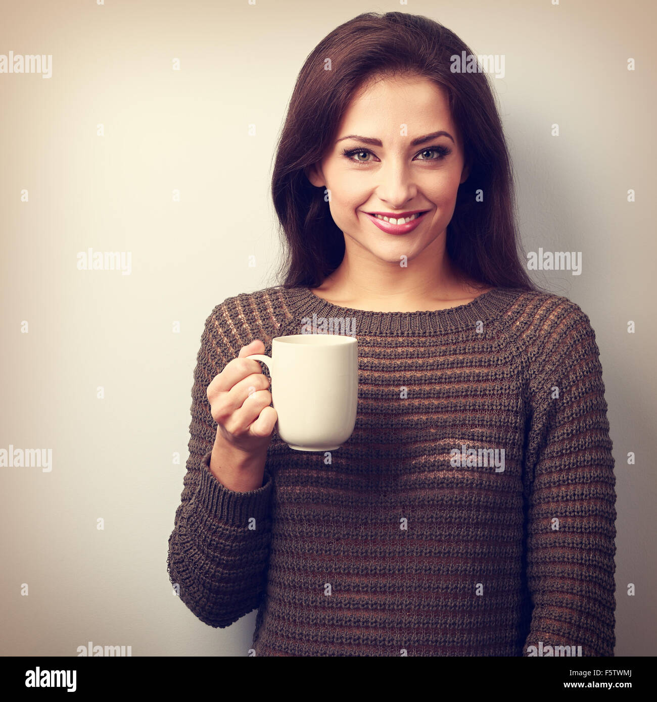 Smiling casual young woman with cup of tea looking happy. Vintage portrait - Stock Image