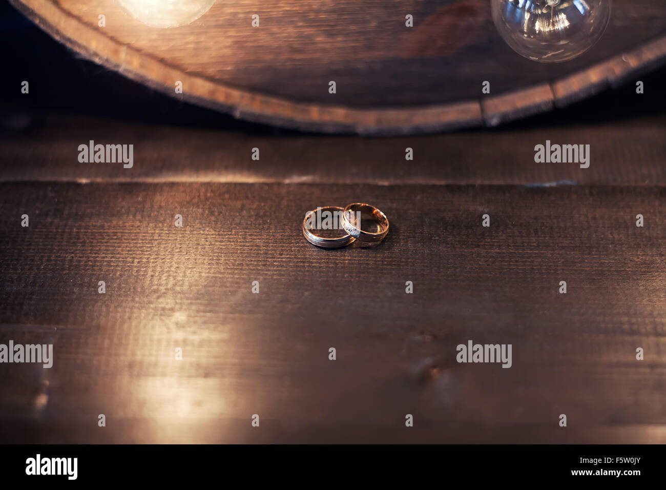 Wedding rings on a wooden table in the lamplight - Stock Image