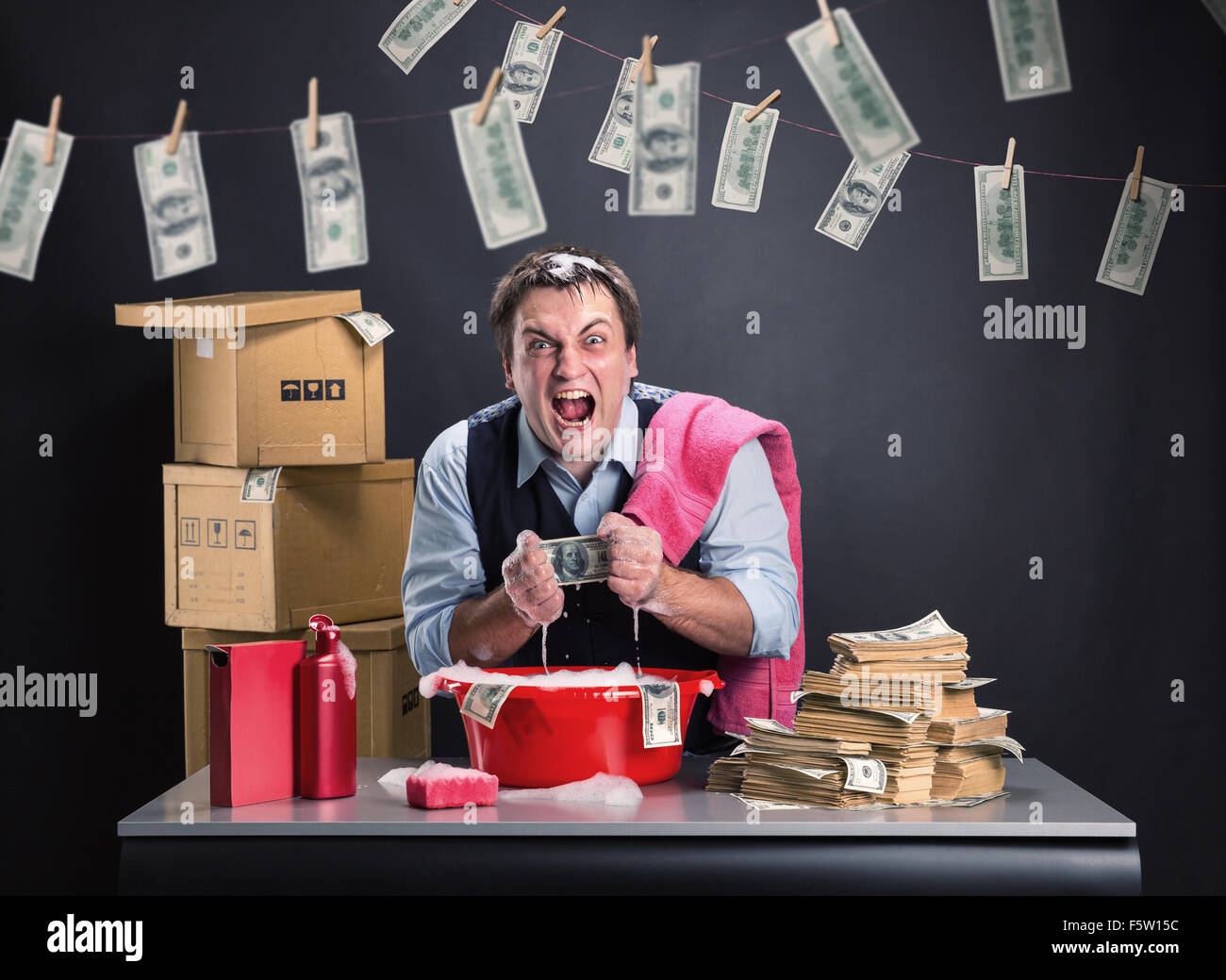 Crazy businessman is laundering money banknotes in foam in red washbowl - Stock Image