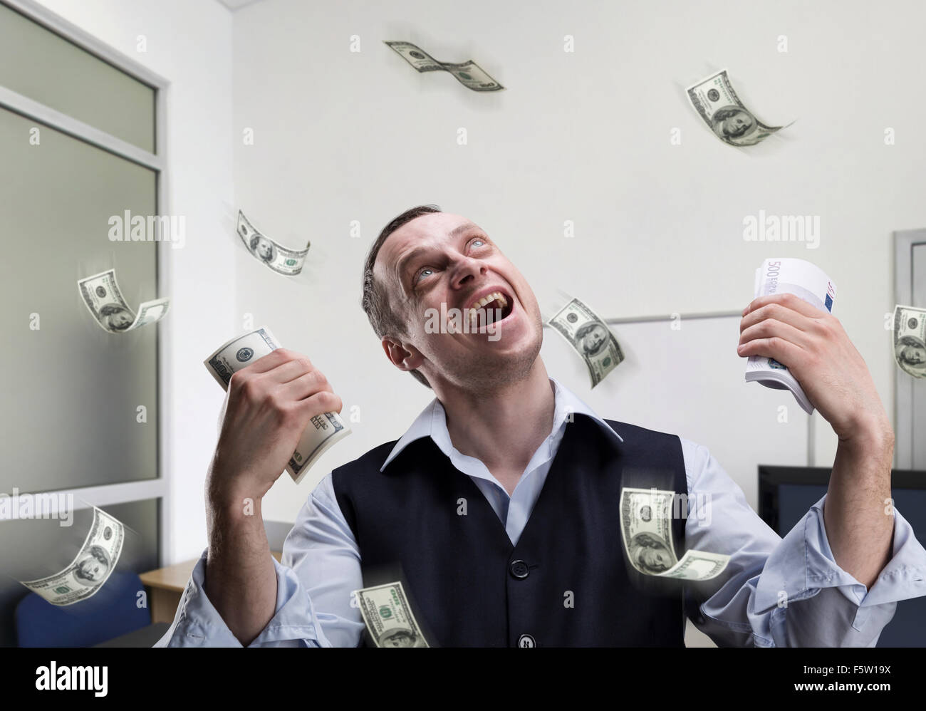 Happy businessman holds money and dreams in the office - Stock Image