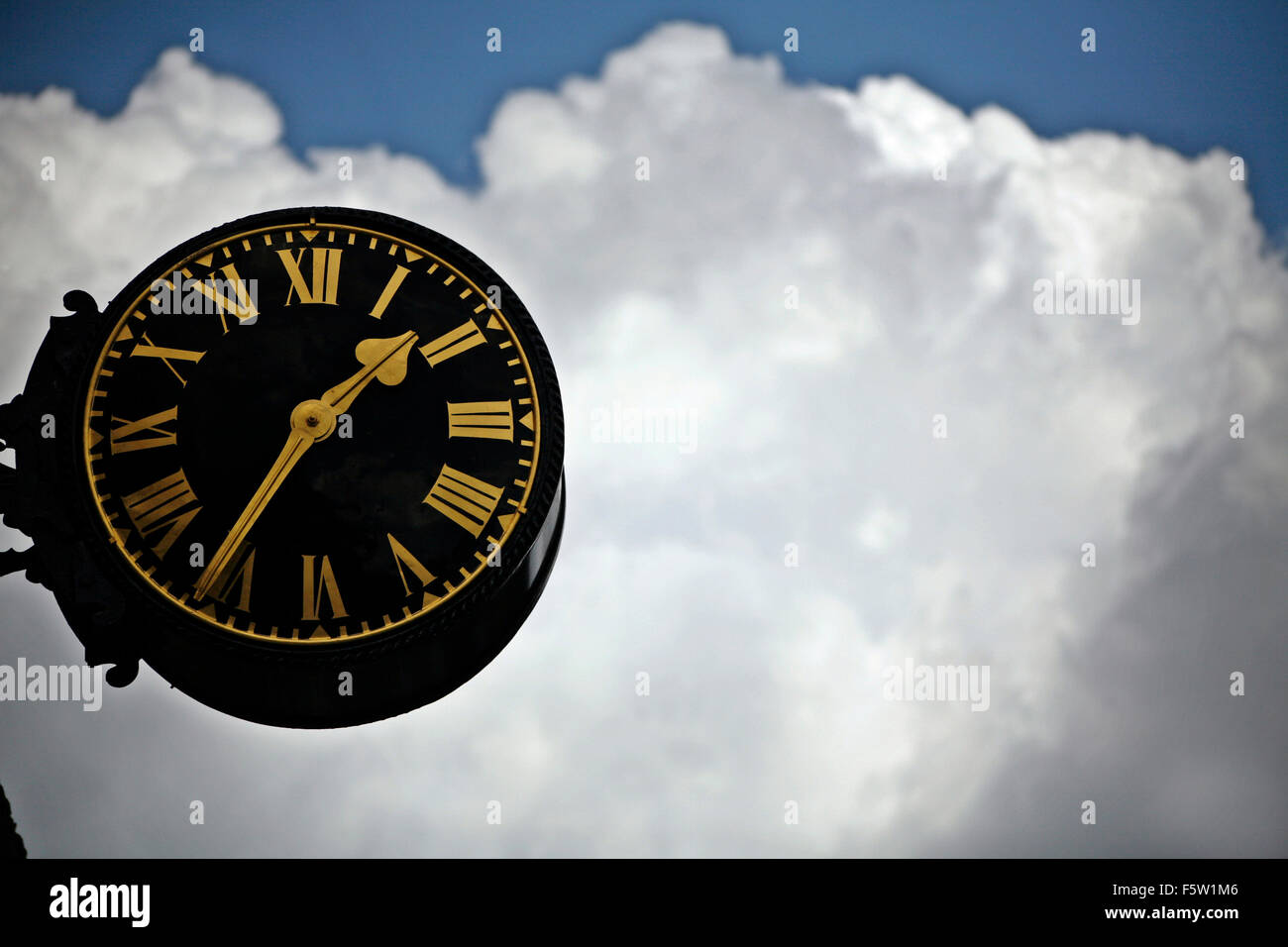Large black clock face with gold roman numerals against blue sky and clouds - Stock Image