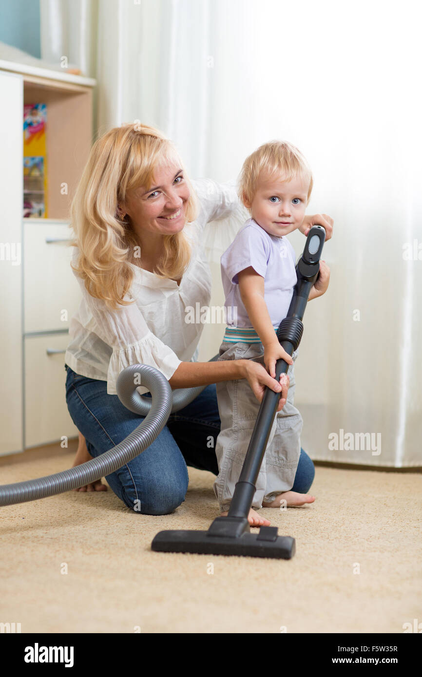 family have fun with cleaning carpeting - housework - Stock Image