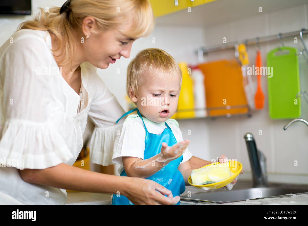 Mother And Son Cleaning Dishes Together - Stock Image