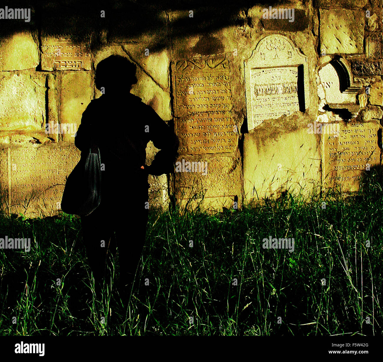 wall made of Jewish headstones in farmers field Poland - Stock Image