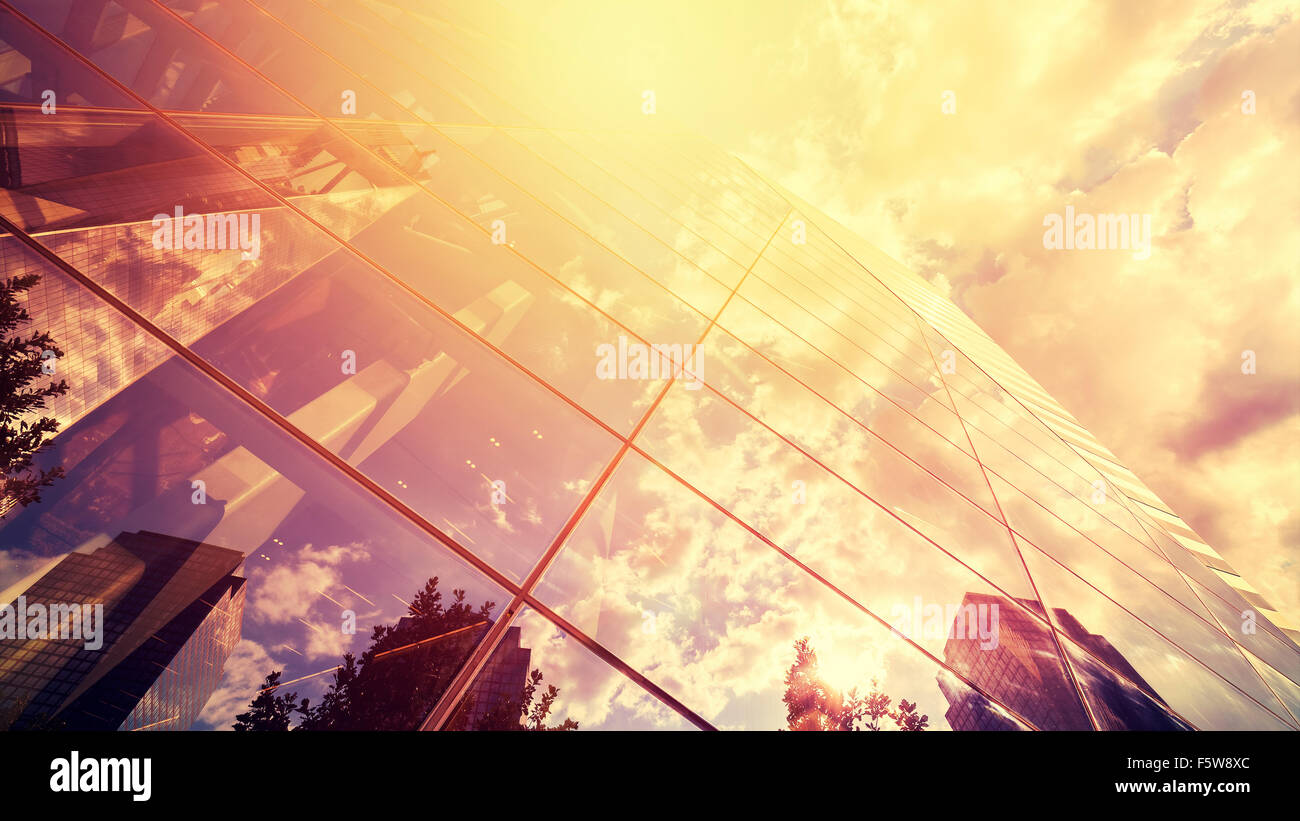 Vintage toned photo of skyscrapers reflection in glass against sun, business background. - Stock Image