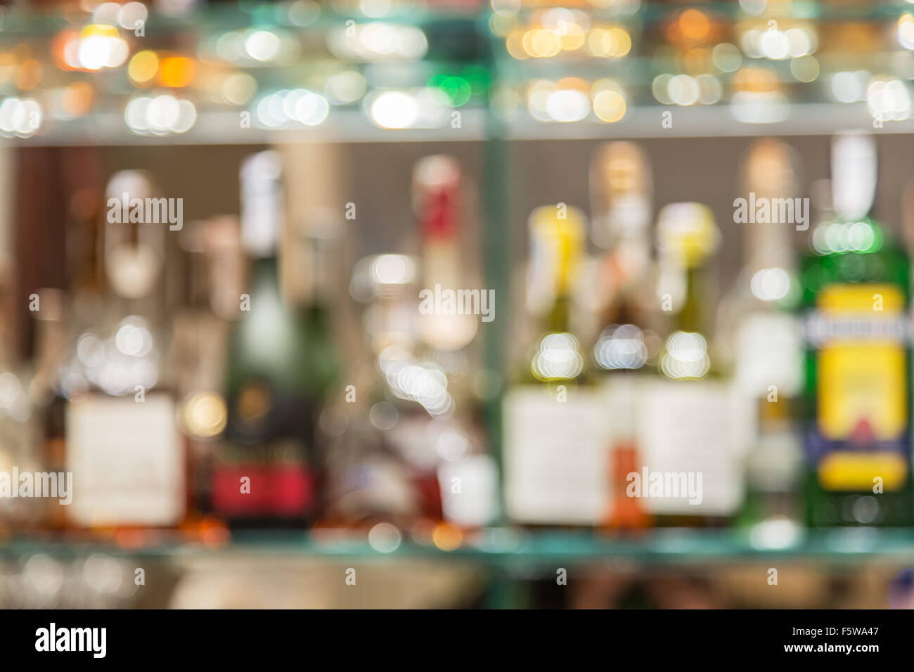 Glass bar counter with blurred shelves with alcohol bottles