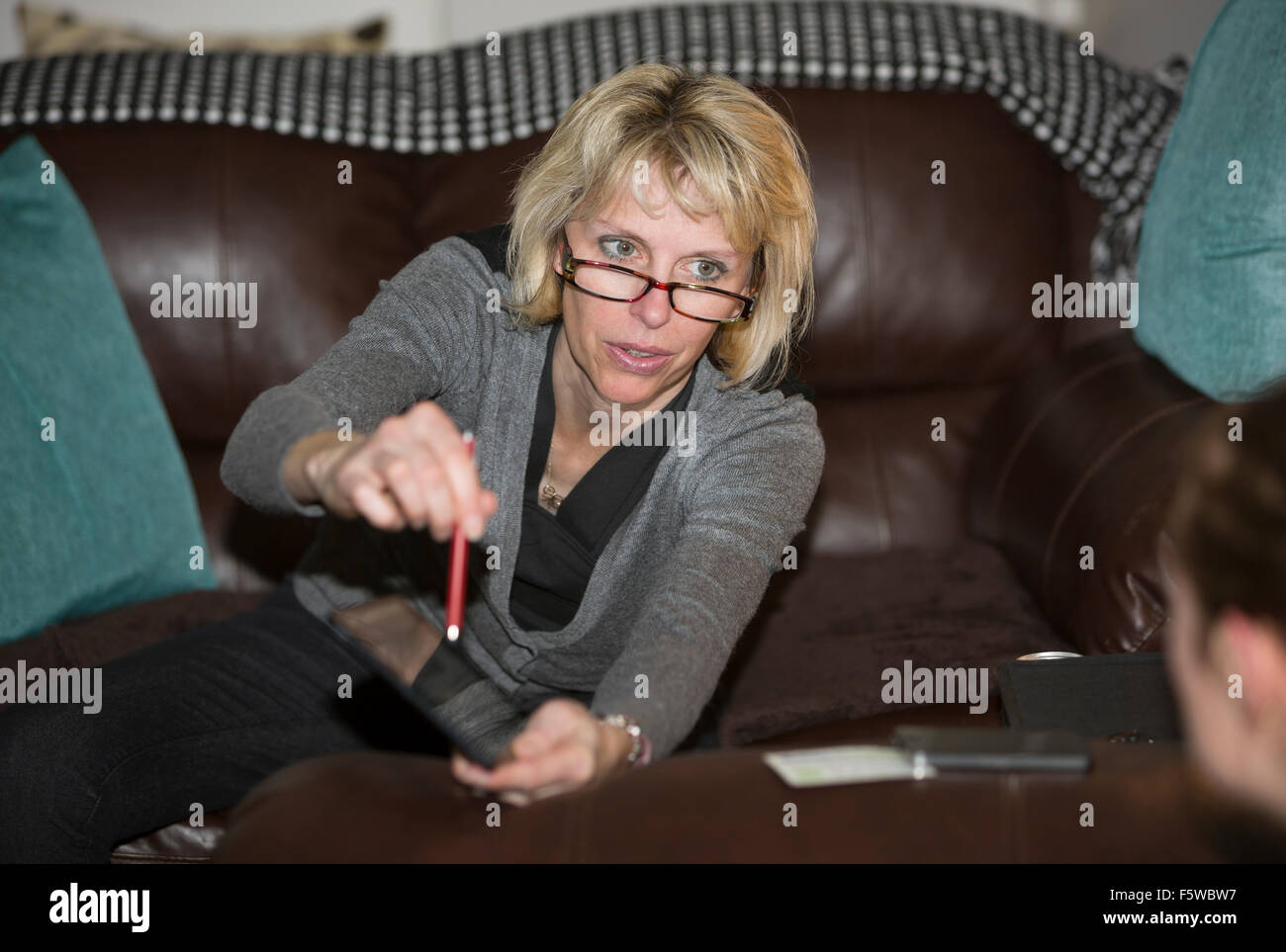 woman showing something on a digital tablet - Stock Image