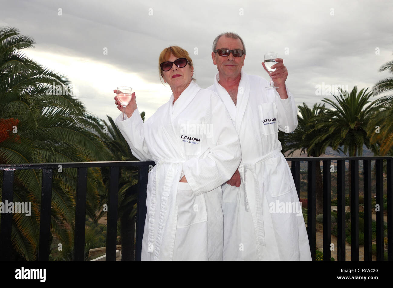 Couple wearing hotel dressing gown robes on balcony - Stock Image