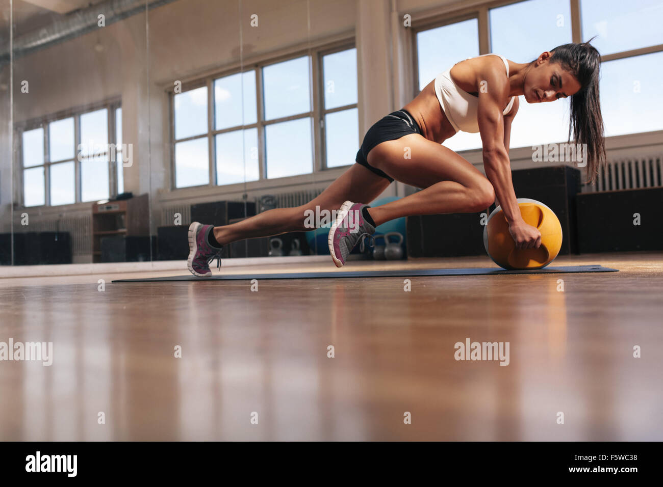 Woman doing intense core exercise on fitness mat. Muscular young woman doing workout at gym. - Stock Image