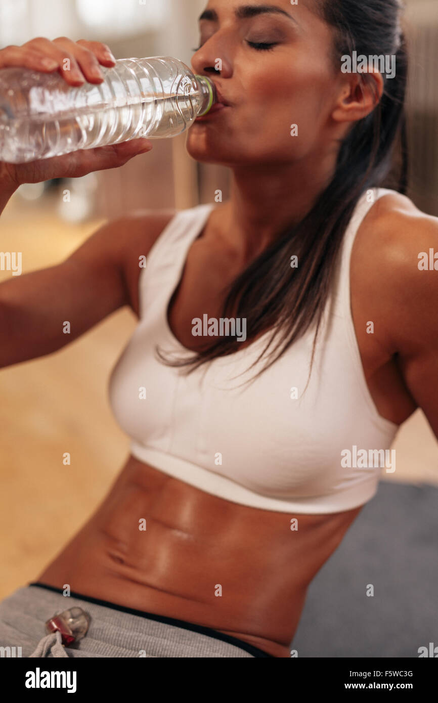 Close up shot of fit young woman drinking water in a break. Female at gym taking a break after fitness training. - Stock Image