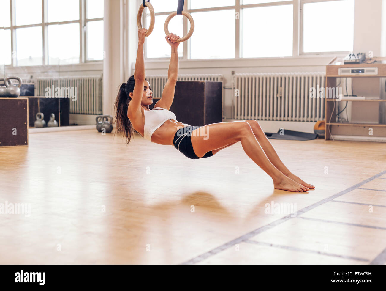 Muscular young woman doing pull-ups on rings. Fit young female athlete exercising with gymnastic rings at gym. - Stock Image