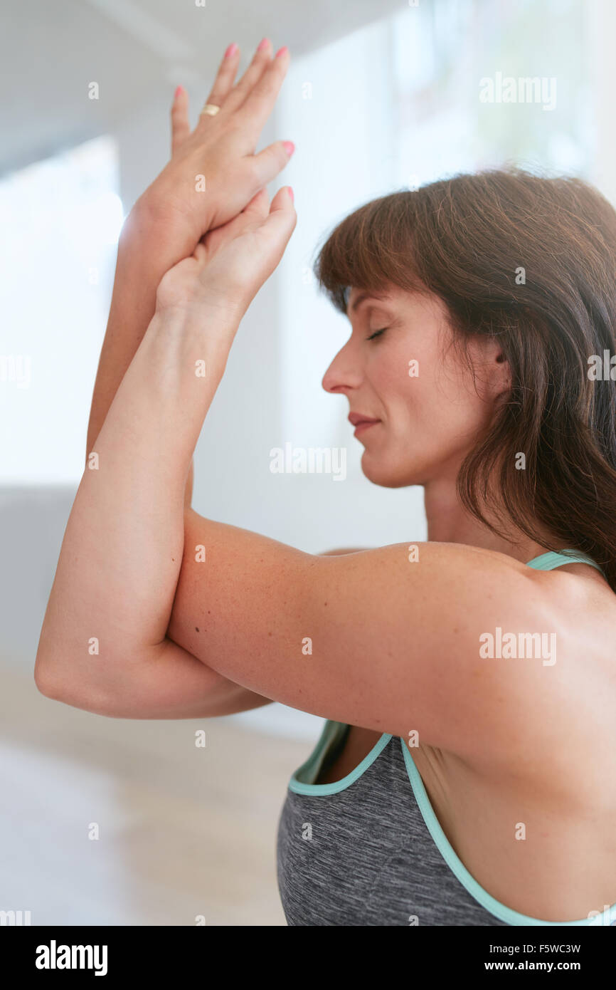 Side view of woman at gym with her crossed arms performing yoga exercise. Garudasana, Eagle pose. - Stock Image