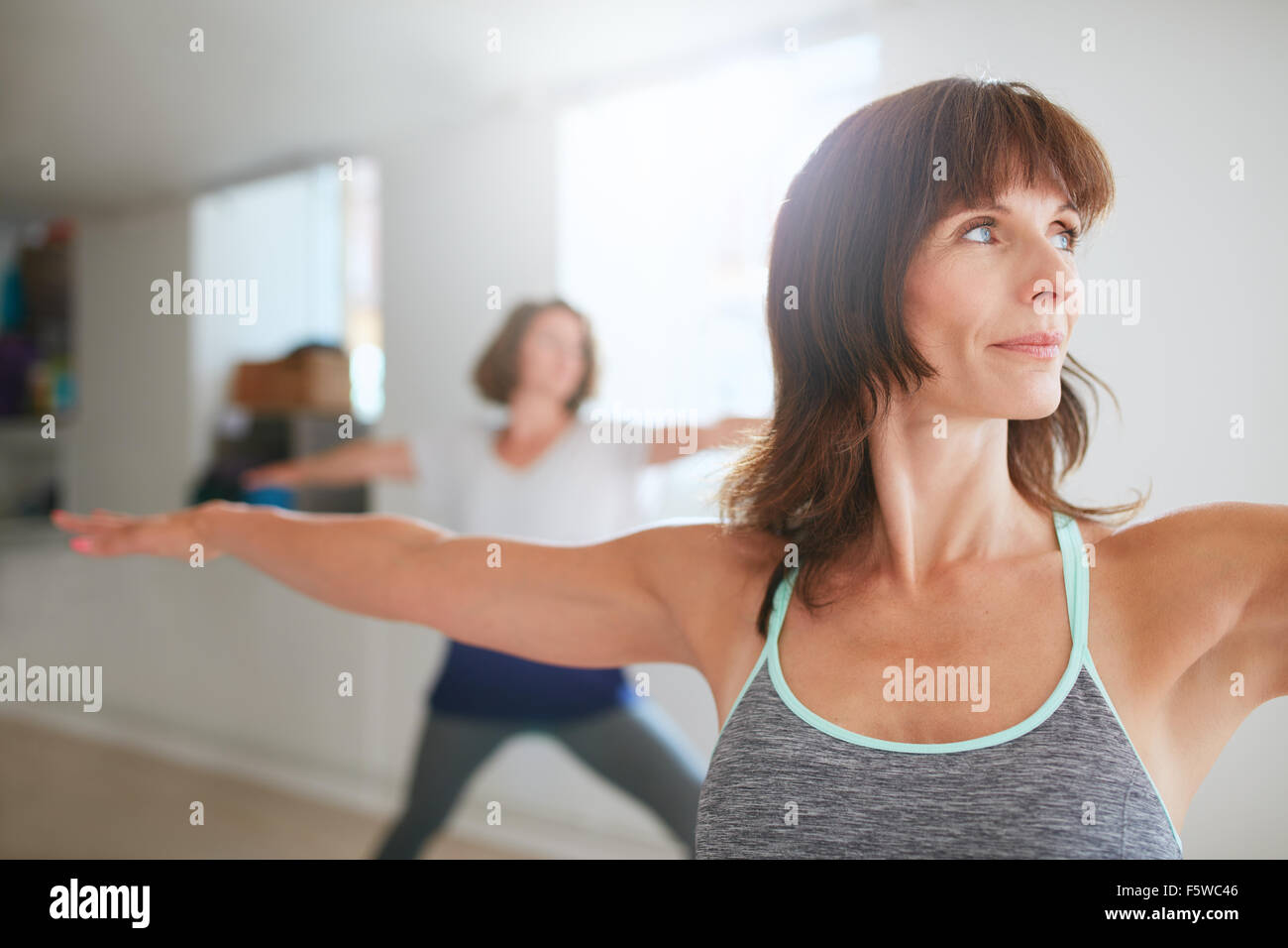 Portrait of beautiful young woman doing the warrior pose during yoga class. Yoga instructor performing Virabhadrasana - Stock Image