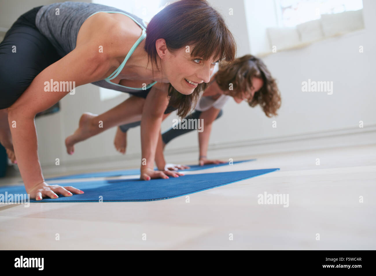 Two women at yoga class doing yoga hand stand pose. Mature woman standing on hands with feet lifted up doing crane - Stock Image
