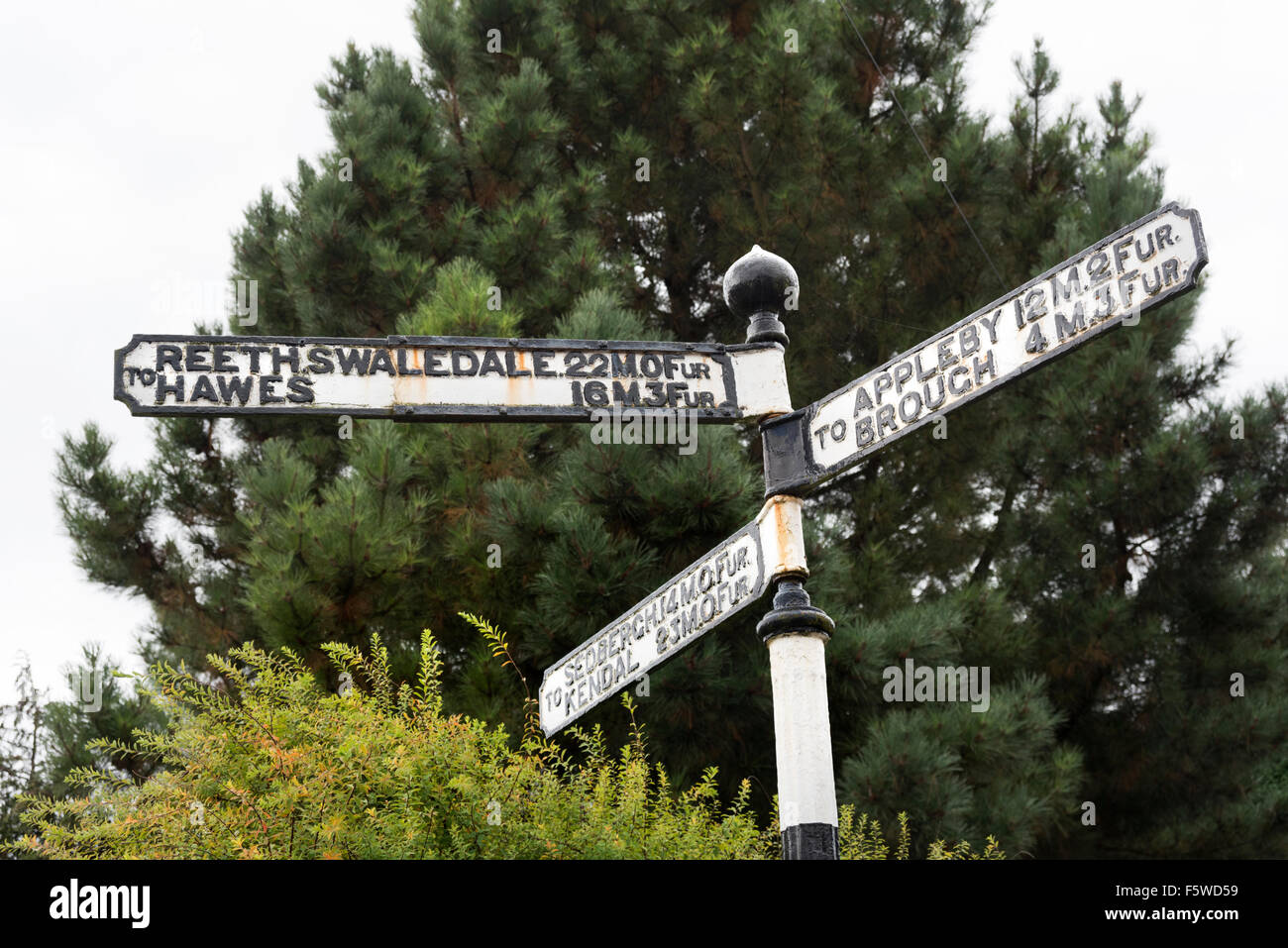 Old road direction sign in miles and furlongs, in the market town of Kirkby Stephen, Cumbria, UK - Stock Image