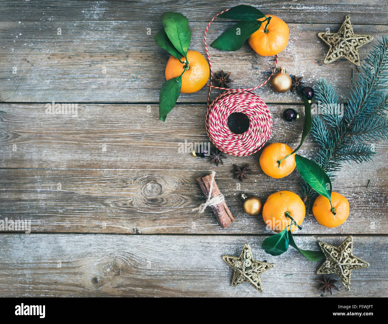 Christmas or New Year decoration background set: fur-tree branches, glass balls, golden glittering toy stars, cinnamon - Stock Image