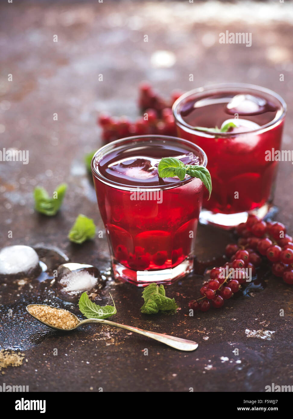 Red berry lemonade with ice and mint on vintage rusty metal backdround, selective focus - Stock Image