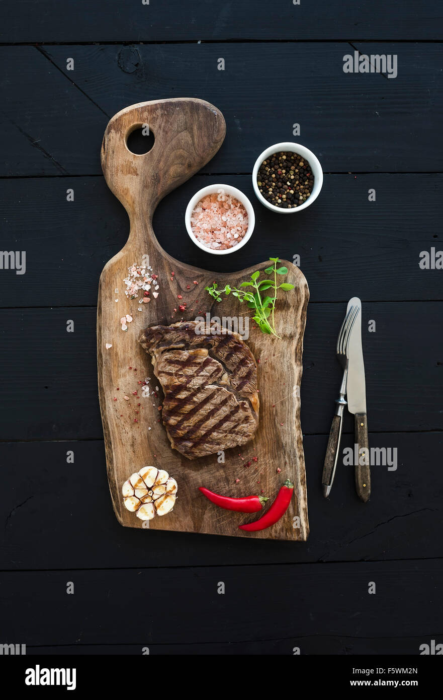 Grilled ribeye beef steak with herbs and spices on walnut cutting board over black wooden background, top view Stock Photo