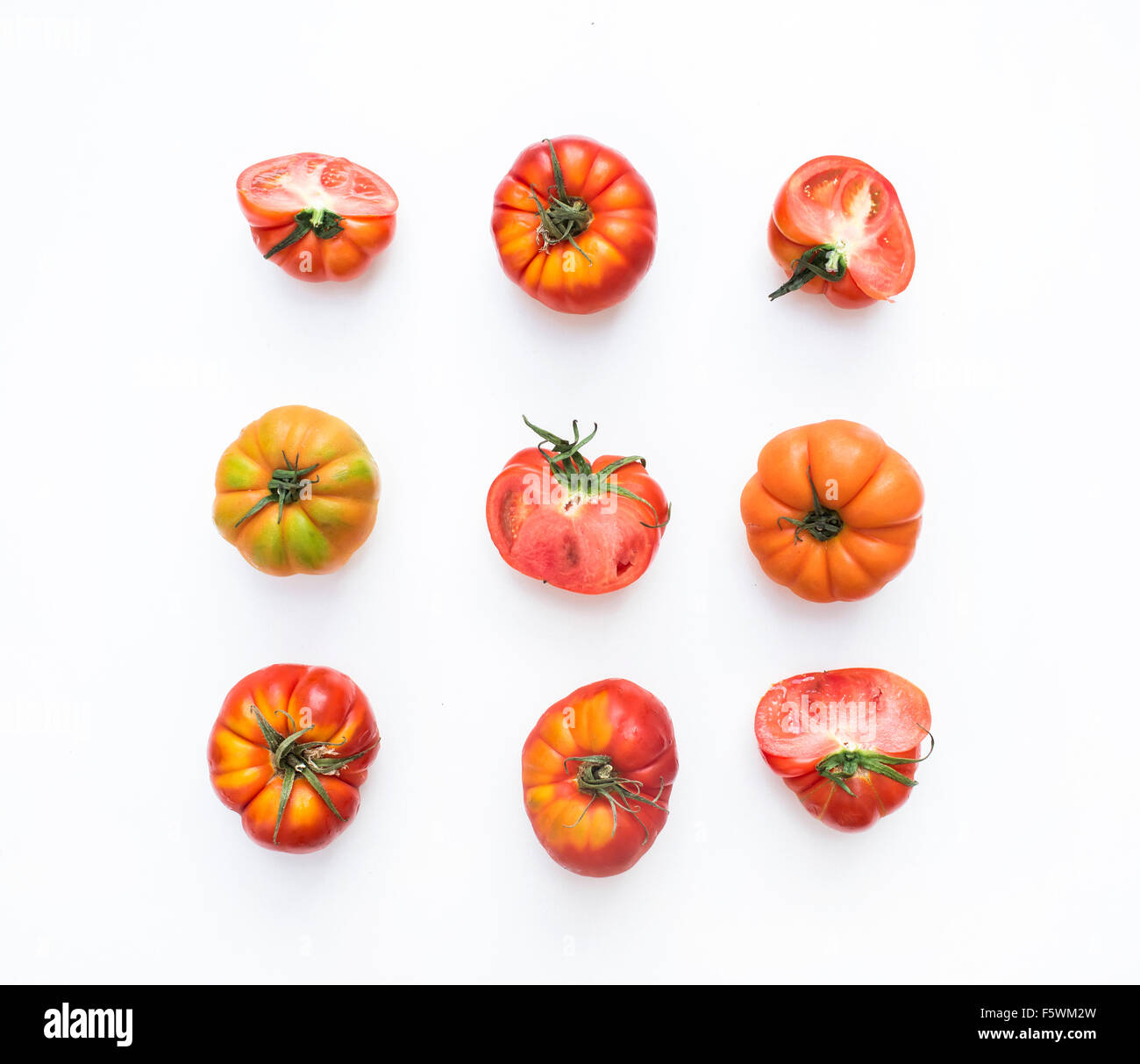 Selection of heirloom tomatoes on a white backdrop, top view - Stock Image
