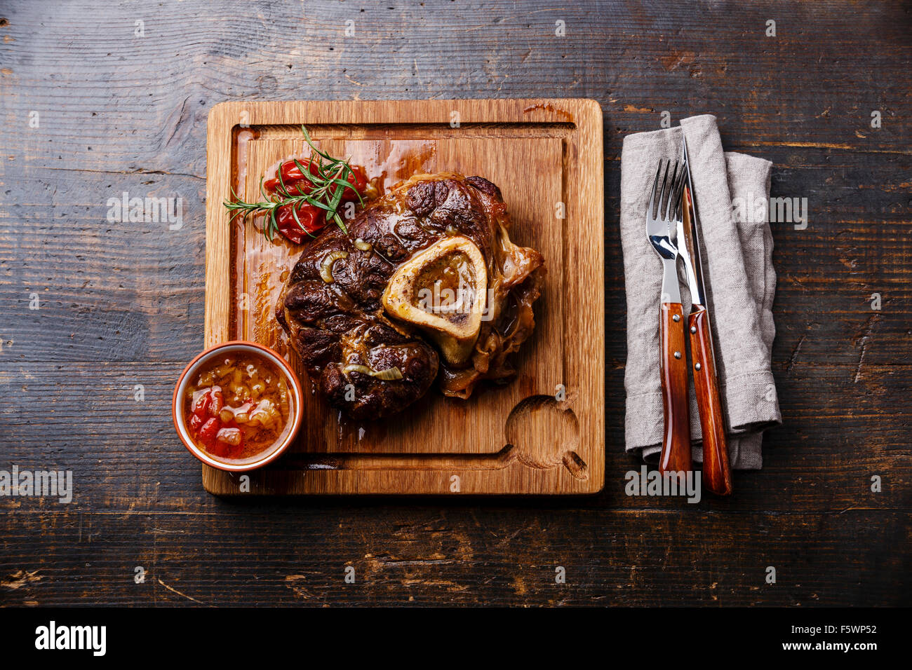 Prepared Osso buco Veal shank with tomatoes on serving board on wooden background - Stock Image