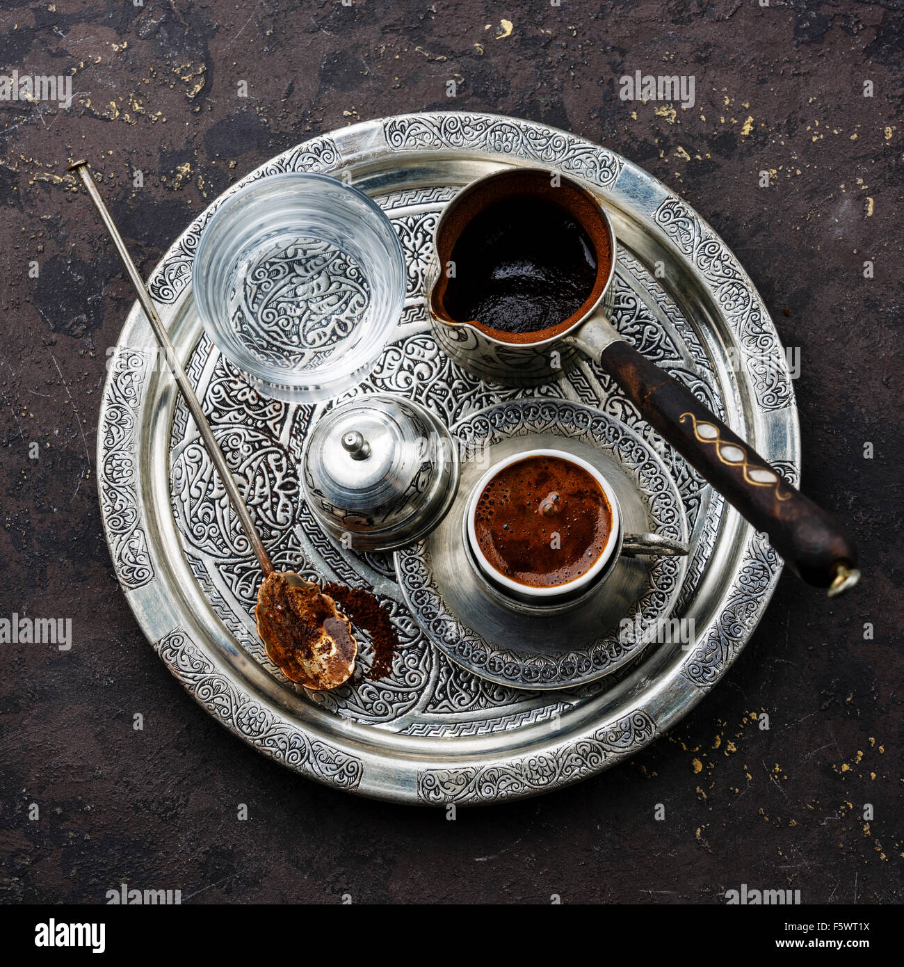 Turkish coffee in coffee pot and cold water on silver tray on black stone background - Stock Image