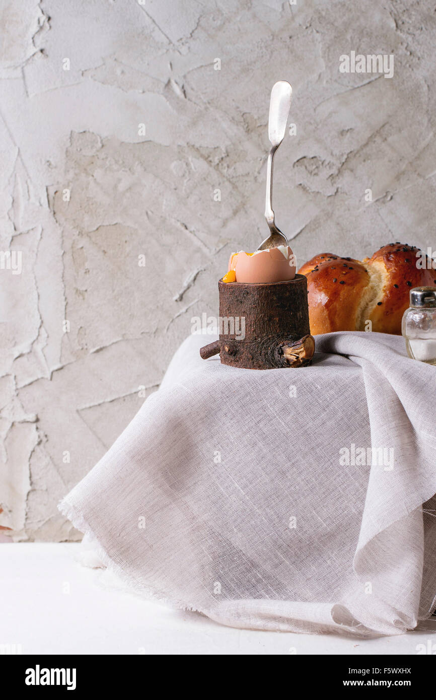 Breakfast with started eating soft-boiled egg with pouring yolk in wooden eggcup and home made bread served with - Stock Image
