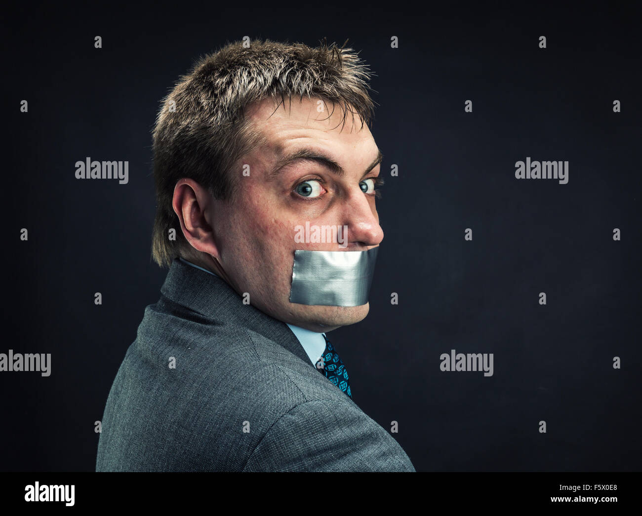 Man with mouth covered by masking tape ,studio shoot - Stock Image
