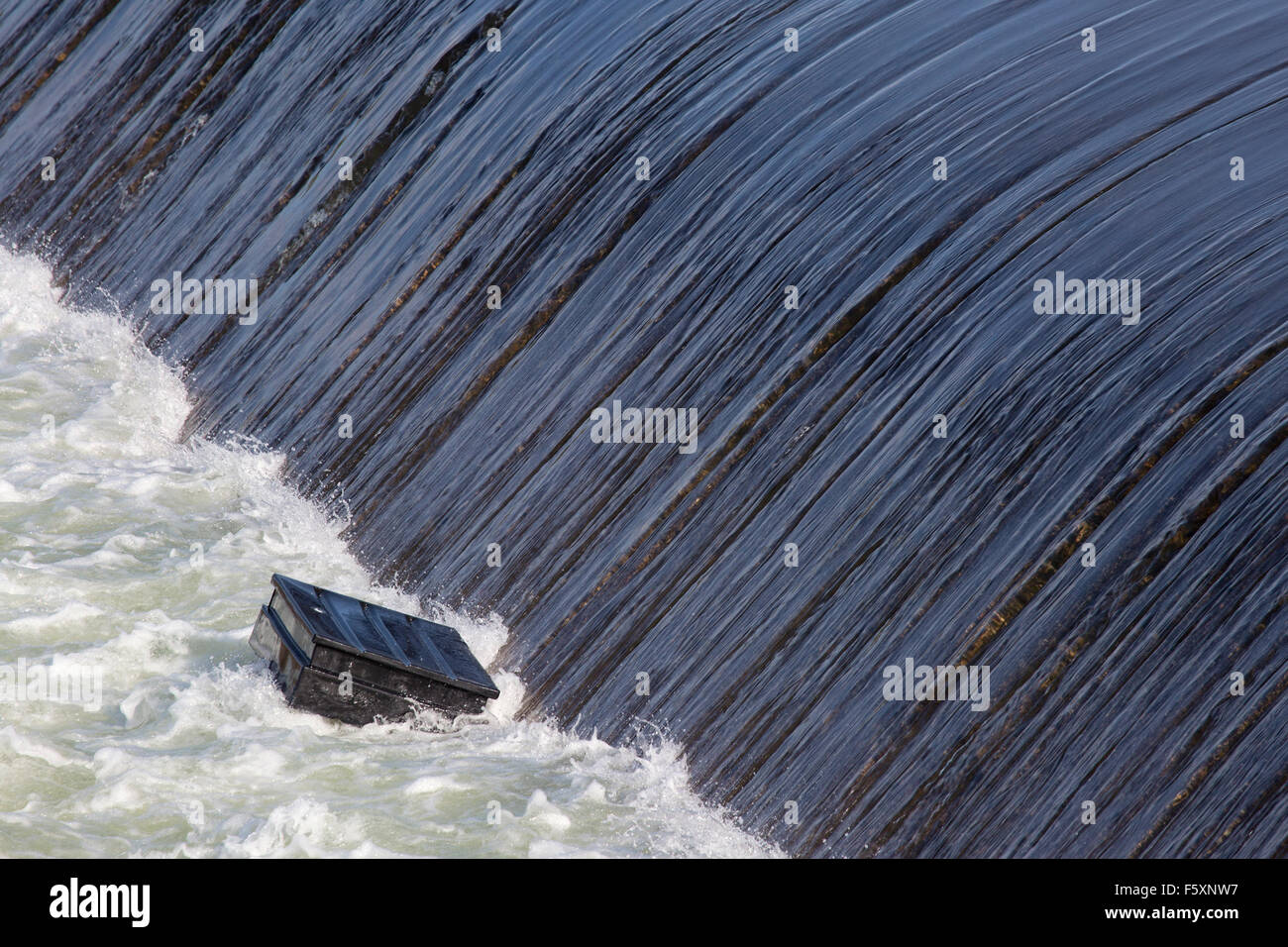 Large item trapped in the powerful recirculating hydraulic wave of a weir on the South Saskatchewan River - Stock Image