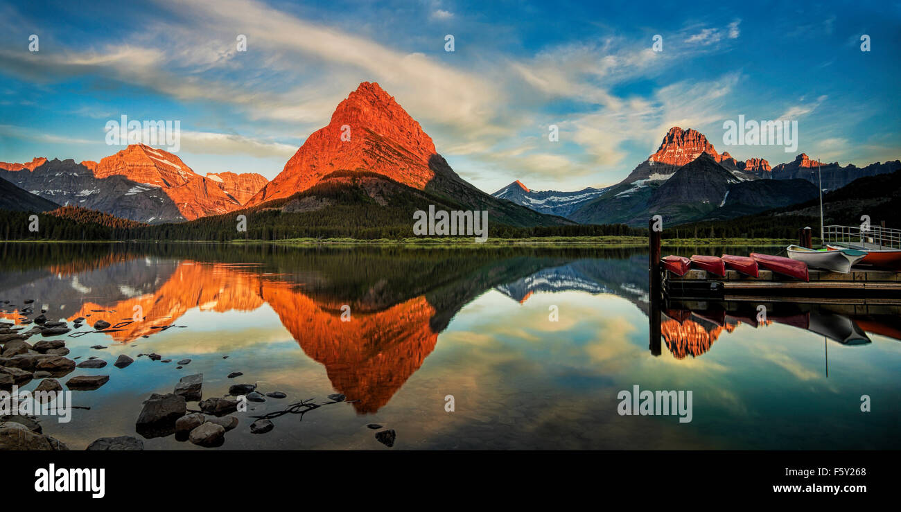 Panorama of Mount Grinnell and its reflection off of Swiftcurrent Lake. - Stock Image