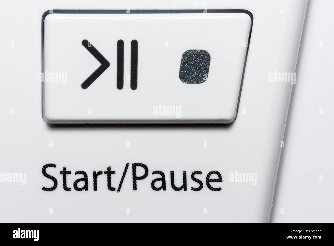 England. Tumble dryer switch, start and pause button with international symbol for start and pause, plus LED light, - Stock Image