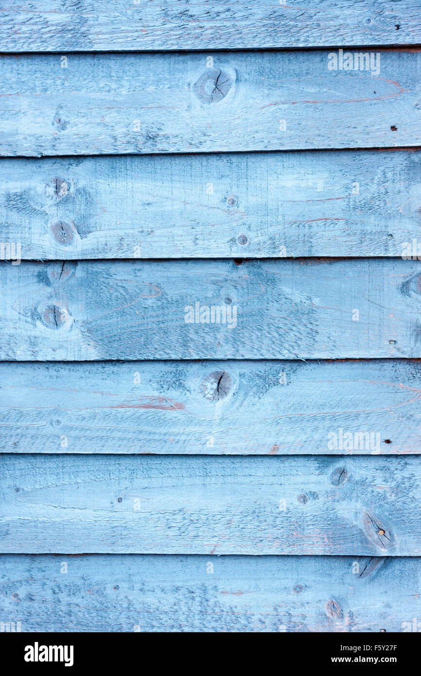 Weathered wooden boards on the side of a Hull of a fishing boat. Blue paint that has faded and weathered in time. - Stock Image