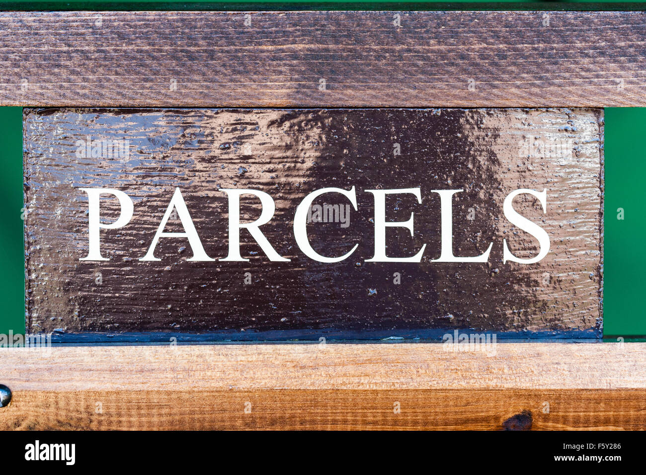 Sign, 'Parcels'. White lettering on dark vanished brass-plate with wooden surround. - Stock Image