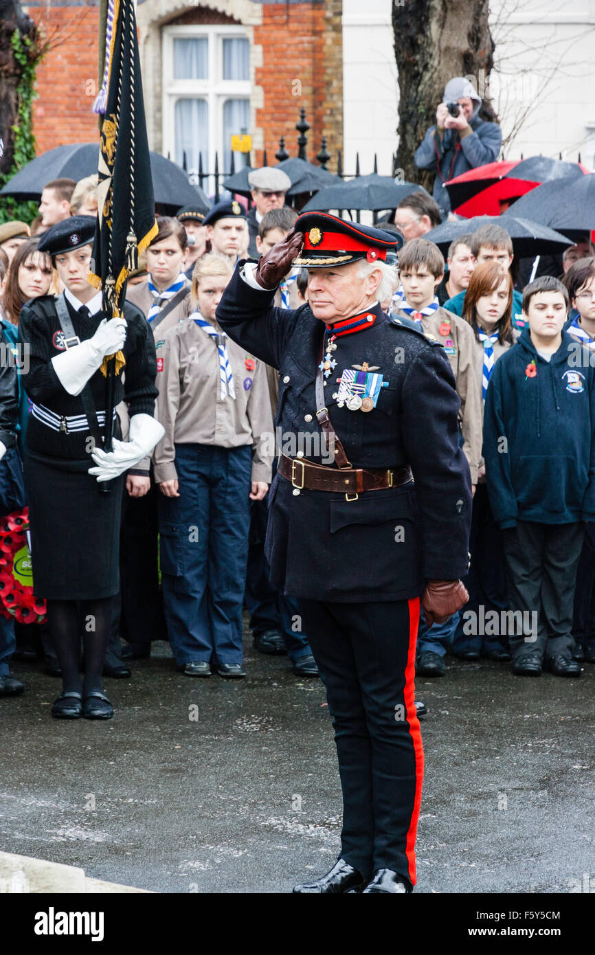 England, Ramsgate. Remembrance Day. Senior military officer saluting at war memorial during ceremony in the rain. - Stock Image