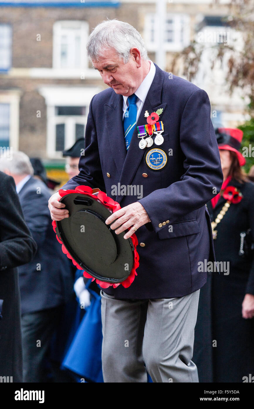 England, Ramsgate. Remembrance Day, November. Mature Ex-serviceman, wearing medals laying poppy wreath at war memorial - Stock Image