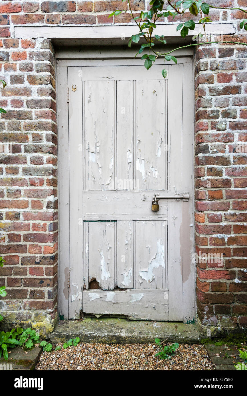 England. Old battered grey panelled door and frame in brick wall ...