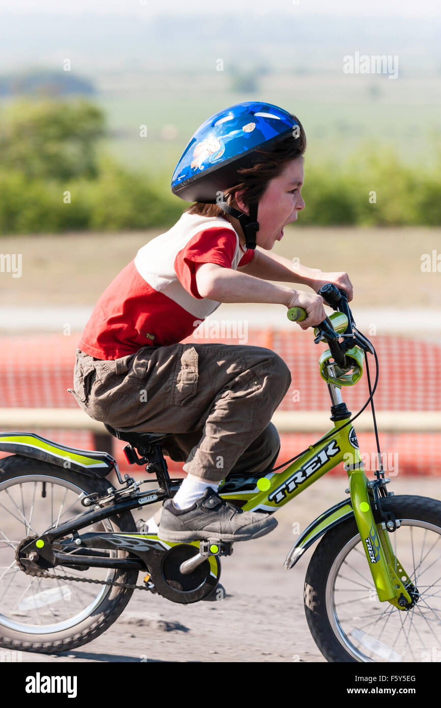 Side view of Caucasian 9 year old child, boy, riding child's bicycle at speed with excited facial expression. - Stock Image